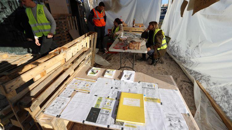 """Des """"gilets jaunes"""" débattent sur un rond-point où a été déposé un cahier de doléances, àCagnes-sur-Mer (Alpes-Maritimes), le 20décembre2018. (VALERY HACHE / AFP)"""
