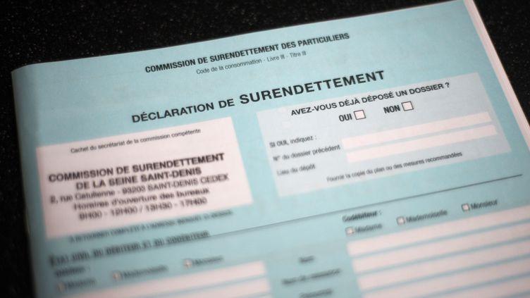 Un dossier de déclaration de surendettement (illustration). (FRED DUFOUR / AFP)