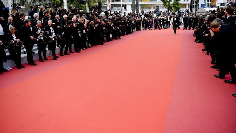 Le tapis rouge du Festival de Cannes entouré de photographes. (CHRISTOPHE SIMON / AFP)