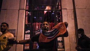 Un supporter du Paris Saint-Germain célèbre la qualification de son équipe pour la finale de la Ligue des champions, le 18 août 2020 à Lisbonne. (PATRICIA DE MELO MOREIRA / AFP)