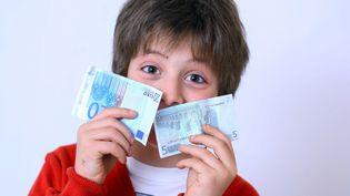 En illustration un garçon heureux de recevoir deux billets en argent de poche, décembre 2009 en France (CLOSON / ISOPIX / SIPA)