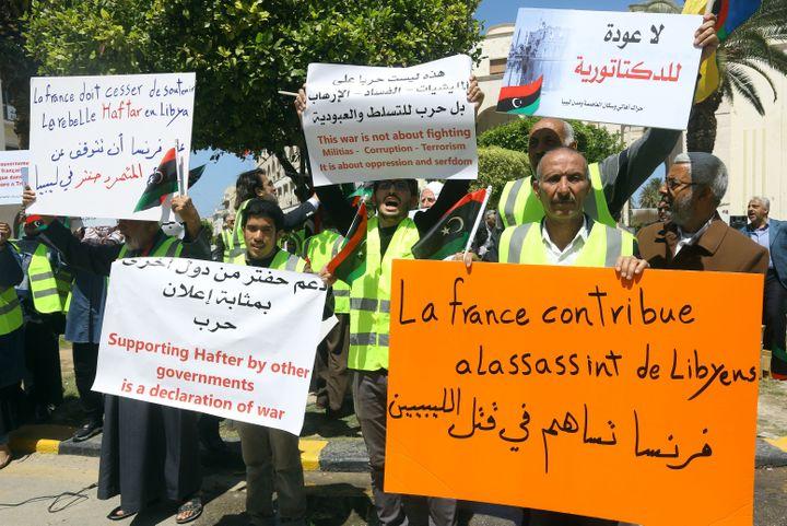 """Des manifestants libyens à Tripoliqui dénoncent le """"soutien"""" de la France au maréchal Haftar, le 16 avril 2019. (MAHMUD TURKIA / AFP)"""
