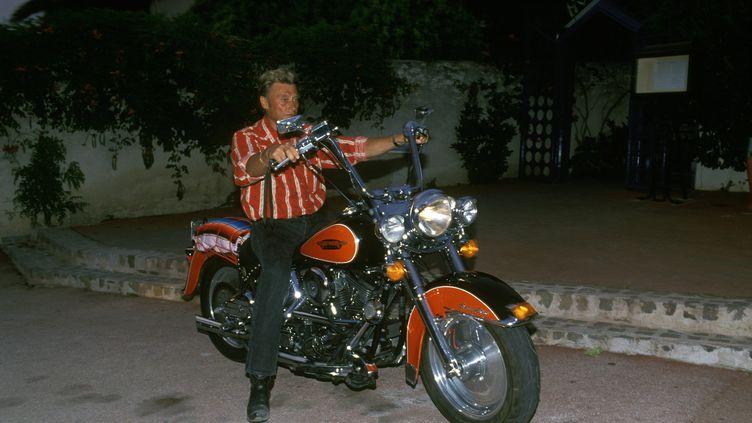 Johnny Hallyday sur une moto Harley-Davidson à Saint Tropez en 1990. (POOL REGLAIN/STEVENS / GAMMA-RAPHO)