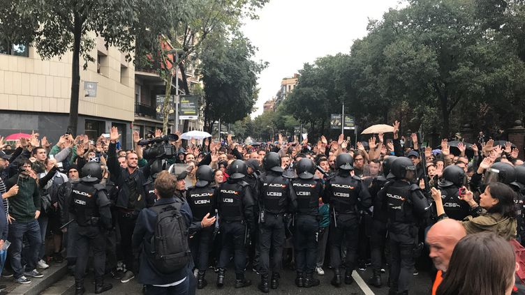 Des policiers bloquent des habitants à Barcelone, dimanche 1er octobre. (ROBIN PRUDENT / FRANCEINFO)