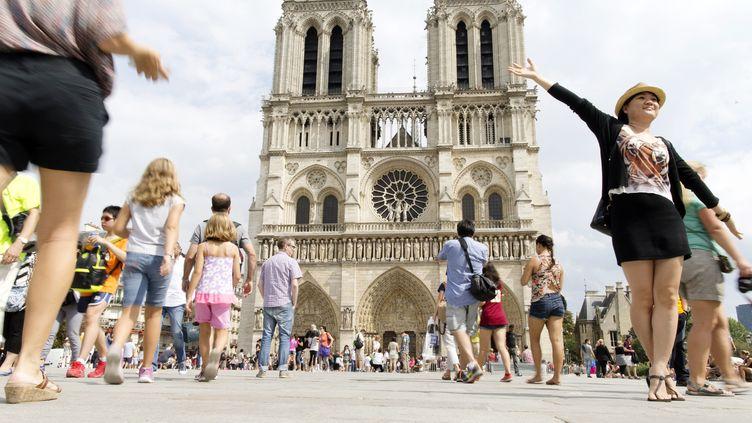 Des touristes sur le parvis de la cathédrale Notre-Dame, à Paris, le 1er août 2014. (KENZO TRIBOUILLARD / AFP)