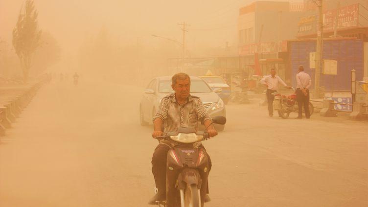 Un homme en motodans une tempête de sable dans la province duXinjiang(Chine), le 18 mai 2016. (REUTERS)