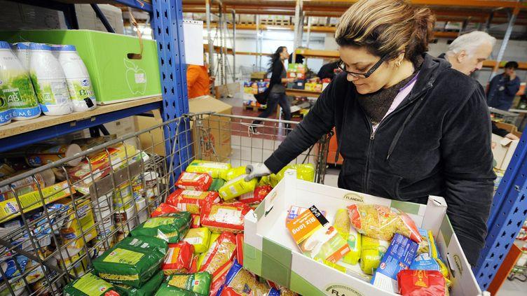 Une bénévole de la Banque alimentaire du Bas-Rhin trie des denrées dans les entrepôts de l'association à Strasbourg, le 26 novembre 2010. (JOHANNA LEGUERRE / AFP)