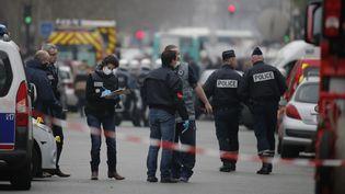 """Des enquêteurs examinent un impact de balle sur un véhicule de police près des locaux de """"Charlie Hebdo"""", à Paris, le 7 janvier 2015. (CHRISTIAN HARTMANN / REUTERS)"""
