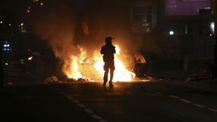 Un policier fait face à un incendie sur la chaussée, le 19 novembre 2018, àSaint-Denis (La Réunion). (RICHARD BOUHET / AFP)