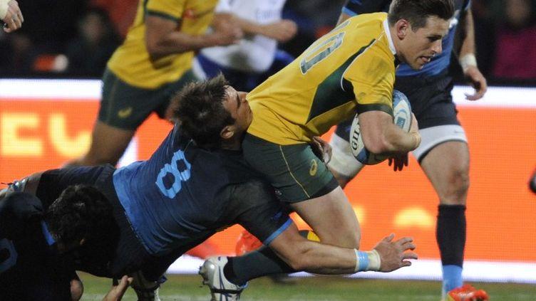 Bernard Foley plaqué par l'Argentin Facundo Isa (ANDRES LARROVERE / AFP)