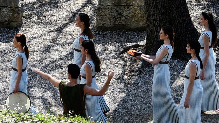 L'actrice grecque Xanthi Georgiou tient la flamme olympique, lorsde la répétition générale de la cérémonie d'allumage de la flamme olympique, dans l'ancienne cité antique d'Olympie, le 11 mars 2020. (AFP)