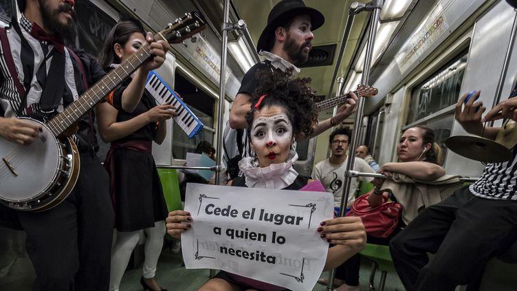 """Une clown de la compagnie Claustrofobos, entourée de musiciens, invite les passager à """"céder la place à ceux qui en ont besoin"""", le 31 mars 2015, à Mexico.  (OMAR TORRES / AFP)"""