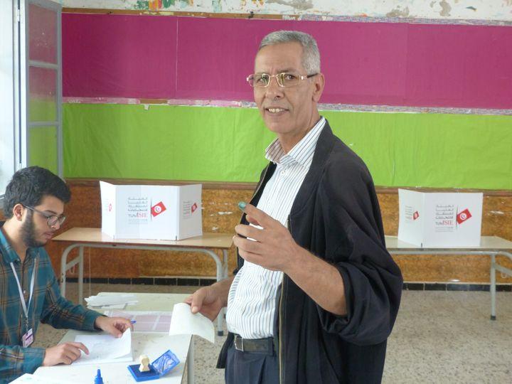 Dans un bureau de vote àEtta(hamen (banlieue de Tunis), lors du 2n tour de la présidentielle le 13 octobre 2019, un électeur montre le bout de son doigt couvert d'encre : la preuve qu'il a accompli son devoir électoral. (AFP - Laurent Ribadeau Dumas)