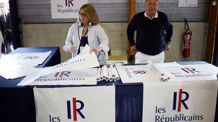 Des membres des Républicains vendent l'affiche du nouveau nom et du nouveau logo de l'UMP. (STEPHANE DE SAKUTIN / AFP)