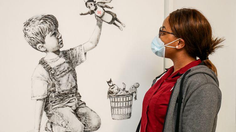 Une employée de l'hôpital de Southampton regarde l'oeuvre offerte par le street-artiste Banksy à l'établissement (7 mai 2020) (STUART MARTIN / UNIVERSITY HOSPITAL SOUTHAMPTON / AFP)