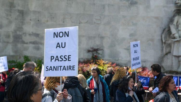 Des pancartes opposées à la création du pass sanitaire lors d'une manifestation à l'appel de l'association Ami entends-tu, à Paris, le 22 mai 2021. (JEROME LEBLOIS / HANS LUCAS / AFP)