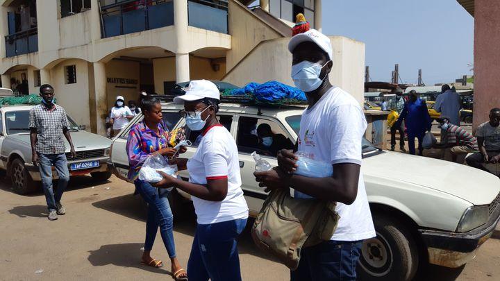 A la gare routière des Baux Maraichers de Dakar (Sénégal), des jeunes distribuent des masques et du gel hydroalcoolique aux voyageurs qui n'en ont pas. (OMAR OUAHMANE / RADIO FRANCE)