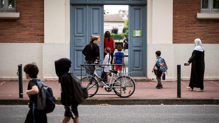 Des parentsetdes enfantsentrent dans une école à Toulouse (Haute-Garonne), le 22 juin 2020. (LIONEL BONAVENTURE / AFP)
