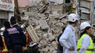 Les secours cherchent d'éventuelles victimes dans les décombres de deux immeubles effondrés situés au 63 et au 65 rue d'Aubagne, à Marseille. (GERARD JULIEN / AFP)