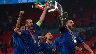 Giorgio Chiellini et Leonardo Bonucci soulèvent fièrement leur premier trophée avec la sélection italienne. (LAURENCE GRIFFITHS / POOL)