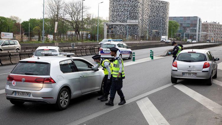 Des policiers procèdent à un contrôle d'autorisation de circuler le 11 avril 2020, à Paris. (THOMAS SAMSON / AFP)