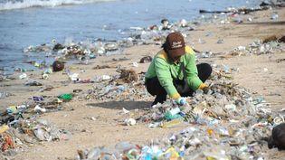 Une plage à Denpasar (Indonésie) polluée par des déchets en plastique est nettoyée à la main. (SONNY TUMBELAKA / AFP)