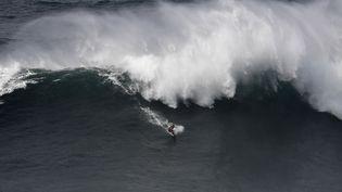Un surfeur affronte une vague de plusieurs mètres de haut à Nazaré, au Portugal, le 21 octobre 2017. (FRANCISCO LEONG / AFP)