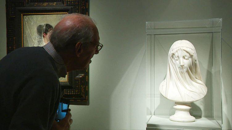 Un visiteur devant une sculpture deGiovanni Strazza , Femme voilée - Le Silence. (M. Zammit / France Télévisions)