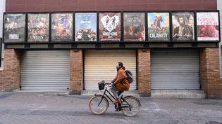 Une femme passe à vélo devant un cinéma fermé à Montpellier(Hérault), le 16 novembre 2020. (PASCAL GUYOT / AFP)