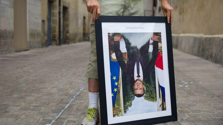 Un hommetient un portrait d'Emmanuel Macron décroché, lors d'une manifestation à Bayonne, le 25 août 2019. (ALEKSANDER KALKA / NURPHOTO)