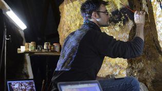 """Un artiste travaille sur une paroi du futur  """"Lascaux 4"""", le 29 février 2016 à Montignac. (MEHDI FEDOUACH / AFP)"""