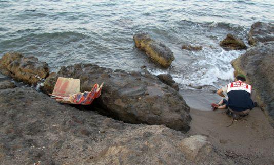 Un gendarme turc se penche sur le corps d'un enfant mort sur une plage de Bodrum (Turquie), le 2 septembre 2015.
