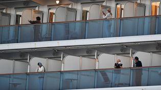 """Des passagers en quarantaine à bord du """"Diamond Princess"""", dans le port de Yokohama, au Japon, mardi 18 février 2020. (CHARLY TRIBALLEAU / AFP)"""