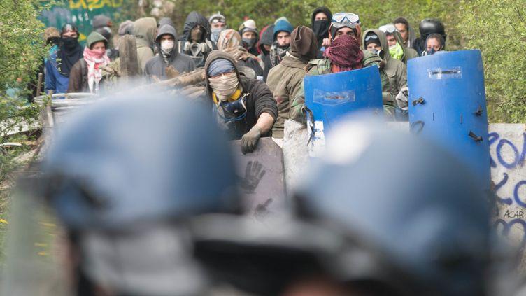 Des zadistes font face à des forces de l'ordre, le 23 avril 2018, sur la ZAD de Notre-Dame-des-Landes. (ESTELLE RUIZ / CROWDSPARK / AFP)