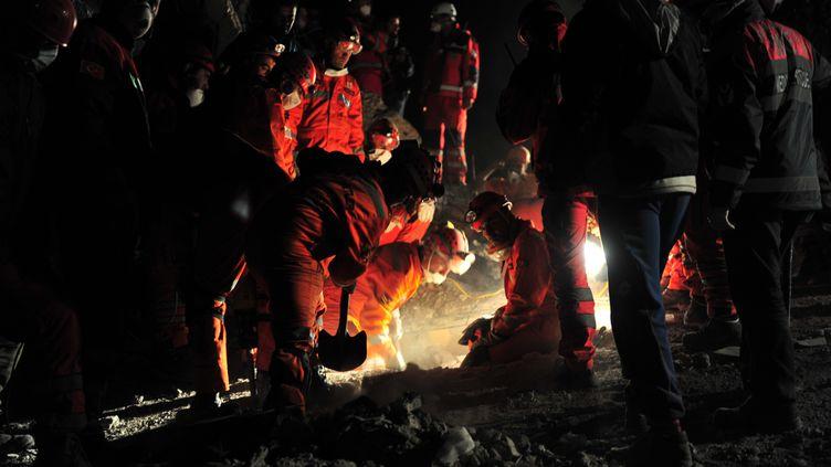 Des secouristes travaillent sur les débris d'un immeuble effondré dans la ville d'Ercis (Turquie), le 26 octobre 2011. (MUSTAFA OZER / AFP)