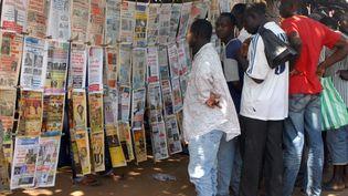 Des habitants de Lomé, au Togo, lisant la presse près d'un marchand de journaux le 11 janvier 2010. (EMILE KOUTON / AFP)