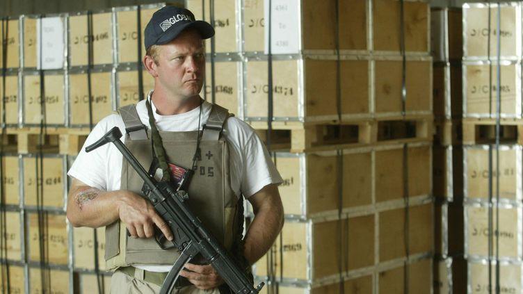 Un employé d'une société de sécurité privée garde un hangar de l'aéroport international de Bagdad (Irak), le 15 octobre 2003. (MARWAN NAAMANI / AFP)