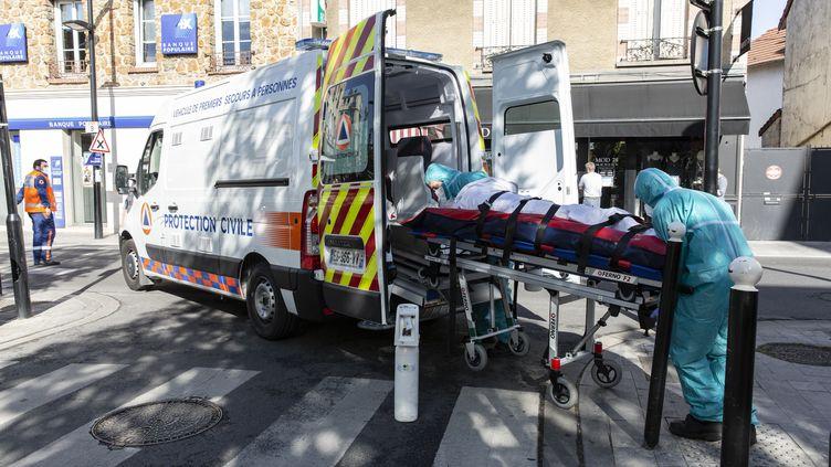 Des membres de la protection civile emmène un patient à bord d'une ambulance, le 18 avril 2020 à Poissy, en région parisienne. (ANTOINE KREMER / HANS LUCAS / AFP)