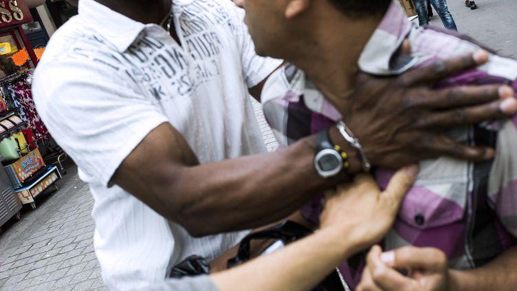 Un homme essaye d'échapper à un contrôle de police dans la rue à Saint-Denis, le 30 juillet 2013. (FRED DUFOUR / AFP)