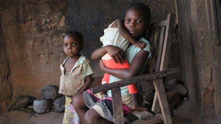 Michèle, 9 ans, tient dans ses bras sa petite sœur d'un an atteinte de malnutrition aiguë. (Save The Children)