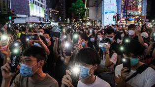 Des manifestants brandissent les torches de leurs téléphones portables, pendant un rassemblement à Hong Kong, le 12 juin 2020. (ANTHONY WALLACE / AFP)