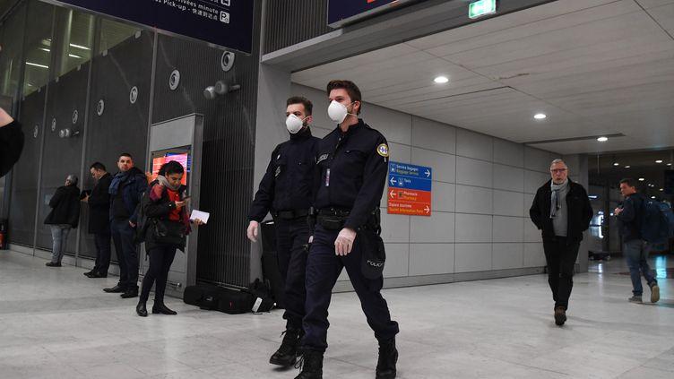 Des policiers patrouillent à l'aéroport Roissy-Charles-de-Gaulle, un masque sur le visage pour se protéger du coronavirus (illustration, 26 janvier 2020). (ALAIN JOCARD / AFP)