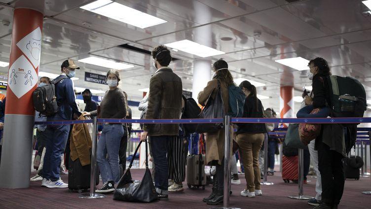 Des passagers patientent dans une file avant le contrôle de leur passeport à l'aéroport Roissy-Charles-de-Gaulle, près de Paris, le 25 avril 2021. (IAN LANGSDON / AFP)