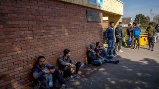 Des migrants kurdes patientent, mardi 11 avril 2017, devant un gymnase réquisitionné pour l'accueil des personnes auparavant installées sur le camp de la Linière, à Grande-Synthe (Nord). (PHILIPPE HUGUEN / AFP)