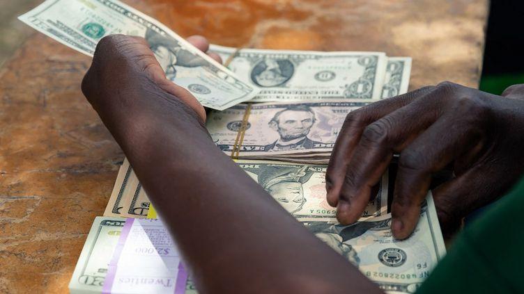 Un agent de sécurité compte des petites coupures en dollars américains dans la zone rurale de Mutoko au Zimbabwe,le 14 mars 2019. (JEKESAI NJIKIZANA / AFP)