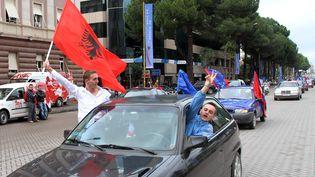 Des Albanais brandissent des drapeaux de l'Albanie et de l'Union européenne, à Tirana, en Albanie, le 8 novembre 2010. (GENT SHKULLAKU / AFP)