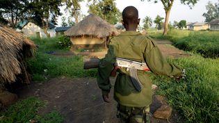Un enfant soldat patrouille avec son arme automatique, près de Bunia, en République démocratique du Congo, le 16 juin 2003. ( JACKY NAEGELEN / REUTERS)