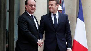 François Hollande serre la main d'Emmanuel Macron sur le perron de l'Elysée, avant de s'entretenir avec lui pendant près d'une heure dans le bureau présidentiel. (BENOIT TESSIER / REUTERS)