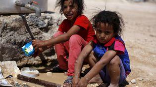 Deux petites Syriennes vont chercher de l'eau dans un camp de érfugiés de Zaatari (Jordanie), le 19 septembre 2015. (MUHAMMAD HAMED / REUTERS)