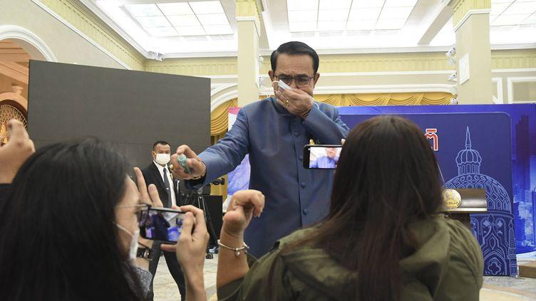 Le Premier ministre thaïlandais,Prayuth Chan-ocha, asperge des journalistes de spray hydroalcoolique, le 9 mars 2021, à Bangkok. (AP/SIPA)